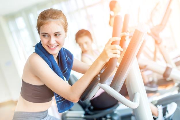 De kaukasische sportvrouw geniet van training met tredmolen in gymnastiekgeschiktheidscentrum met groep mensen