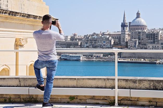 De kaukasische studentenmens erachter met smartphone neemt foto van valletta-horizon
