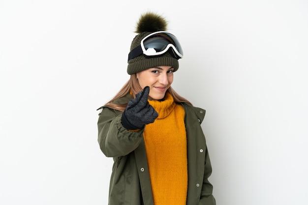 De kaukasische vrouw die van de skiër met snowboardglazen op witte achtergrond wordt geïsoleerd die geldgebaar maakt