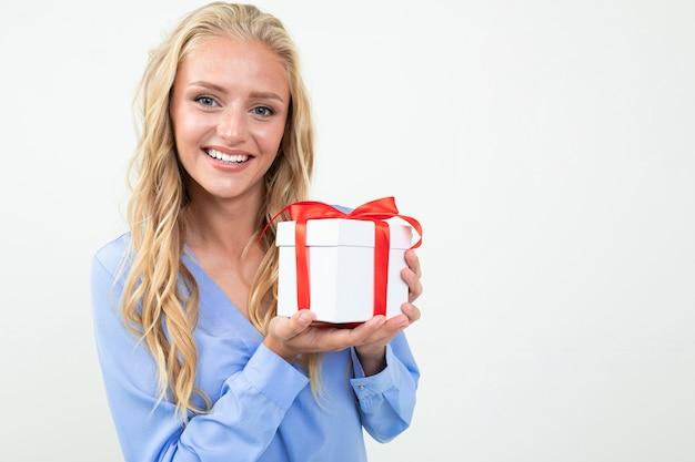 De kaukasische vrouw houdt witte doos met gift en glimlacht, portret dat op wit wordt geïsoleerd