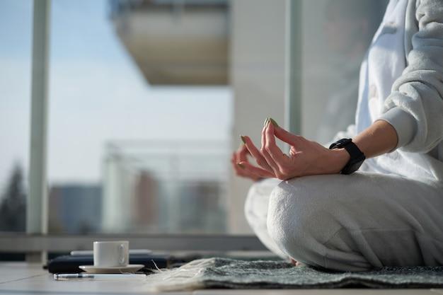 De kaukasische vrouw mediteert in pyjama's zittend in lotuspositie op plaid vóór het werk