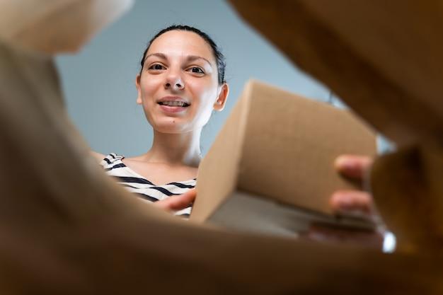 De kaukasische vrouw opent ambachtdocument leveringspakket met gelukkige emotie.