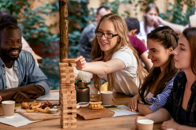 De kaukasische vrouw zet een baksteen aan een lange toren bij jenga van het tafelspel in het restaurant