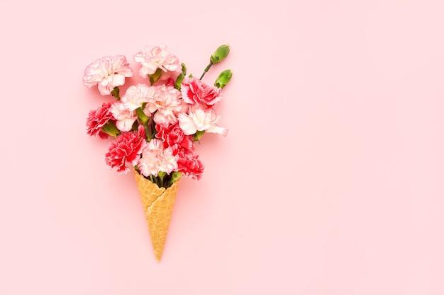De kegel van het wafelroomijs met rode anjerbloemen op roze muur. zomer concept. kopieer de ruimte, bovenaan