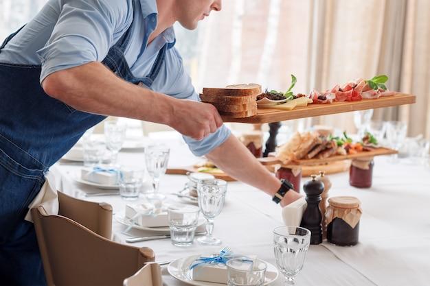 De kelner die vleesschotels op houten raad dienen bij restaurant, sluit omhoog mening.