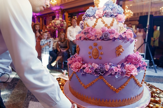 De kelner draagt luxueuze violette verfraaide huwelijkscake
