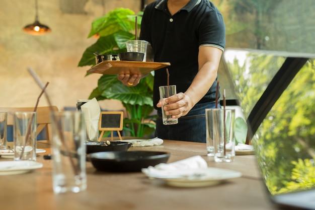De kelner haalt met de hand lege glazen en vuile vaat op dinerrestaurant op.