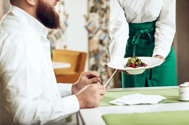 De kelner van het meisje dient zijn schotel in restaurant aan een man