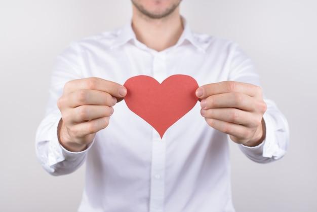 De kerel die rood document hart houdt isoleerde grijze achtergrond