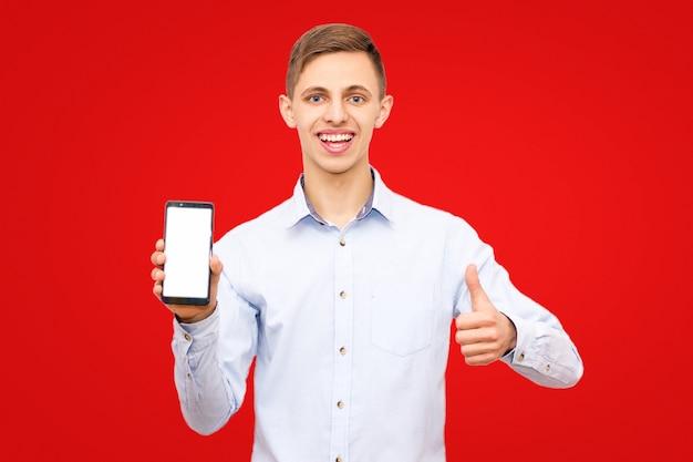 De kerel in een blauw overhemd adverteert een telefoon die op een gele achtergrond in de studio wordt geïsoleerd, die duim toont