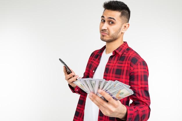 De kerel in een geruit overhemd meldt het winnen van geld telefonisch op een witte achtergrond met exemplaarruimte