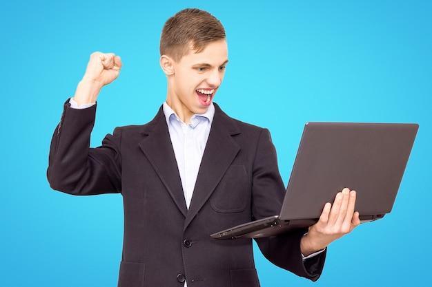 De kerel in een jasje en een blauw overhemd met laptop verheugt zich, geïsoleerd op een blauwe achtergrond
