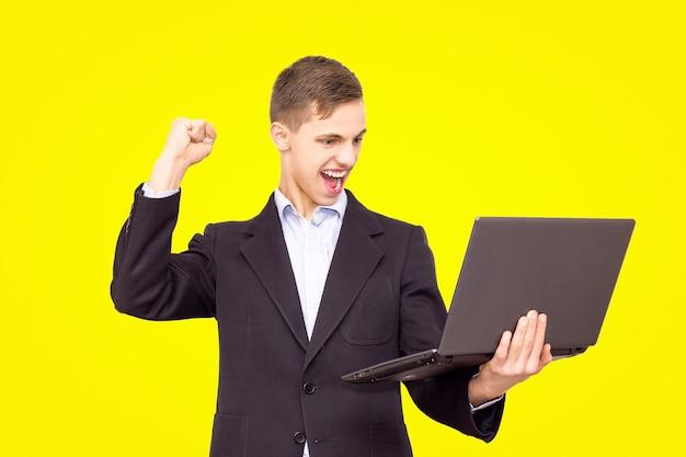 De kerel in een jasje en een blauw overhemd met laptop verheugt zich, geïsoleerd op gele achtergrond