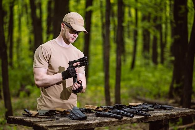 De kerel in het bos test zijn wapens voor het schieten van sporten