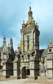 De kerk en de ingang van de parochie sluiten. saint-thegonnec, bretagne, frankrijk. lente uitzicht.