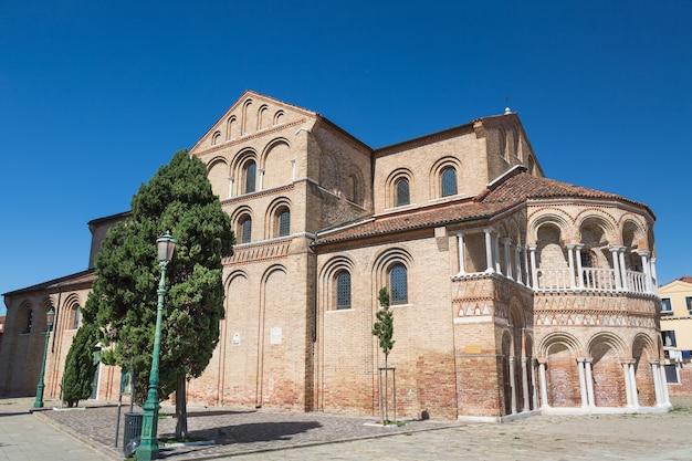 De kerk van santa maria e san donato op murano island in de venetiaanse lagune met blauwe hemel.