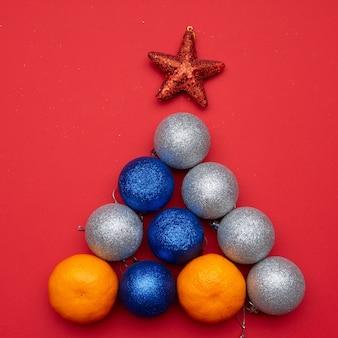 De kerstboom is gemaakt van mandarijnen en kerstballen. het concept van het nieuwe jaar.