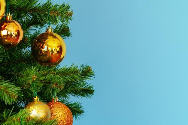 De kerstboom met gouden snuisterijen sluit omhoog op blauwe achtergrond