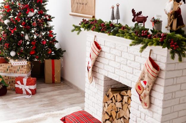 De kerstboom staat in de buurt van cadeautjes