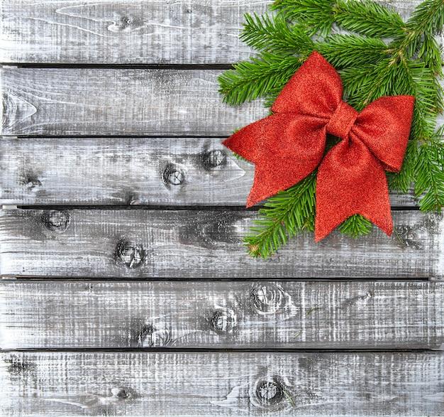 De kerstboom vertakt zich de rode rustieke houten achtergrond van de lintboog