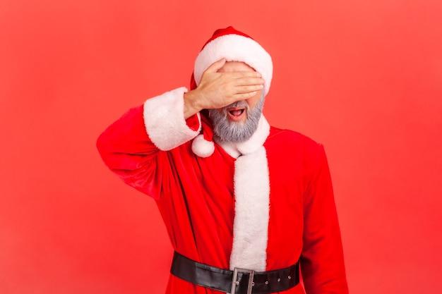 De kerstman bedekt de ogen met de handpalm, wil niet zien en vermijdt problemen.