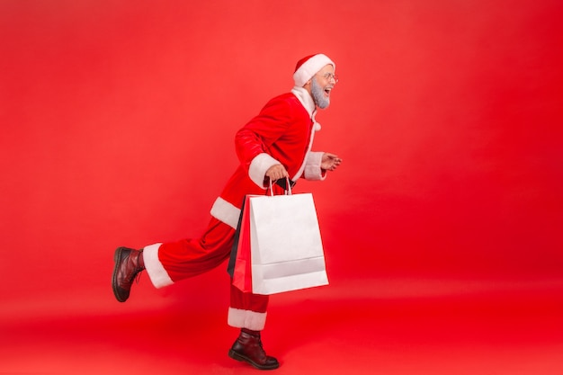 De kerstman beweegt met boodschappentassen, cadeautjes voor kerstmis.