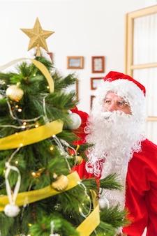 De kerstman die de bovenkant van de kerstboom met ster verfraait