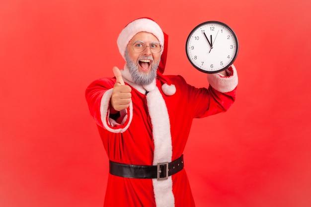 De kerstman die de wandklok toont en met de vinger naar de camera wijst, heeft een verbaasde uitdrukking.