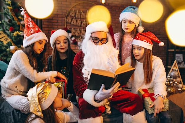 De kerstman die een boek leest aan een groep jonge geitjes