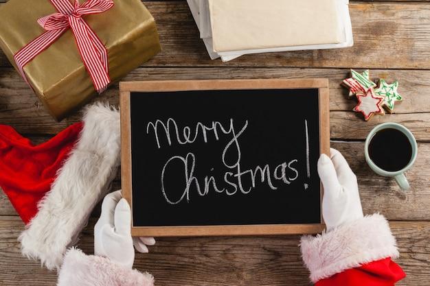 De kerstman die een lei met vrolijke kerstmisteksten houdt