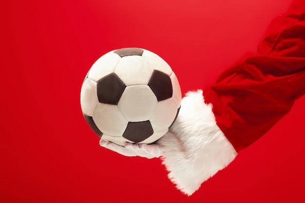 De kerstman die een voetbalbal houdt die op rode studioachtergrond wordt geïsoleerd
