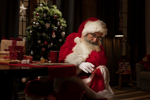De kerstman die kerstcadeaus voorbereidt