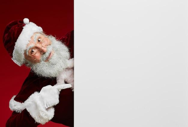 De kerstman die op wit teken richt