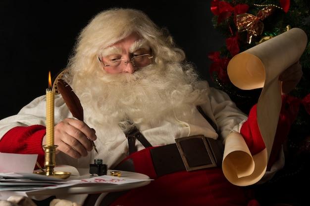 De kerstman die thuis en op oud document broodje zitten om lijst met veerpen en inkt te doen