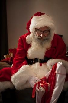 De kerstman die zijn zak van giften voorbereidt
