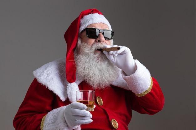 De kerstman draagt een zonnebril die een sigaar rookt en een garde drinkt op een donkere achtergrond