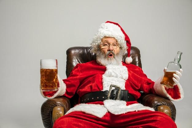 De kerstman drinkt bier zittend op een fauteuil, feliciteert, ziet er dronken en gelukkig uit. kaukasisch mannelijk model in klederdracht. nieuwjaar 2020, geschenken, feestdagen, winterstemming. copyspace voor uw advertentie.
