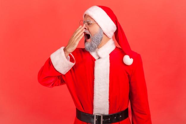 De kerstman gaapt en bedekt de mond, slaperig na een slapeloze nacht, gebrek aan energie.