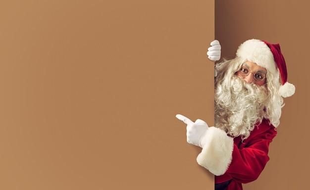 De kerstman geeft een lege ruimte aan voor uw kersttekst