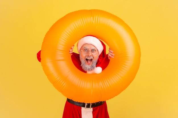 De kerstman heeft een geschokte uitdrukking verbaasd, terwijl hij wintervakanties viert in een warm resort.