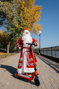 De kerstman heeft haast op een scooter met cadeautjes voor de vakantie aan de kinderen.