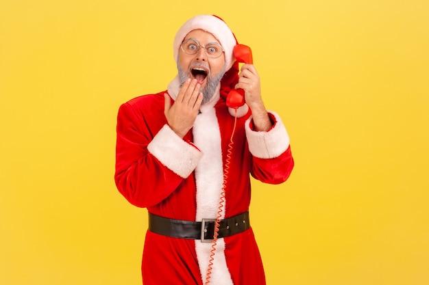 De kerstman houdt de handset vast, beantwoordt de oproep van de klant met een geschokte uitdrukking, bedekt de mond.