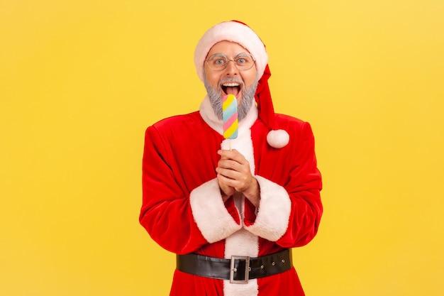 De kerstman houdt en bijt veelkleurig ijs vast en viert de wintervakantie.