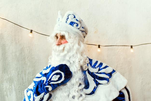 De kerstman in een blauwe bontjas kijkt uit het raam, denkt en raakt zijn baard aan.