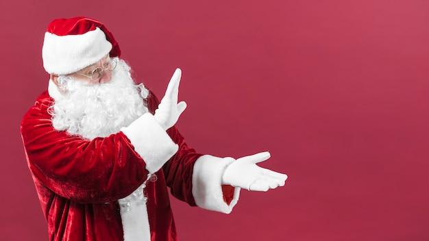 De kerstman in glazen die iets met handen tonen