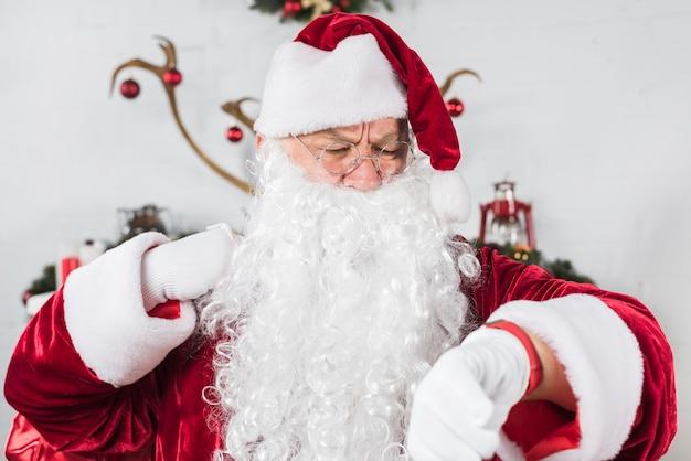 De kerstman in glazen die tijd controleren op polshorloge