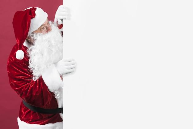De kerstman in glazen die uit witte muur kijken