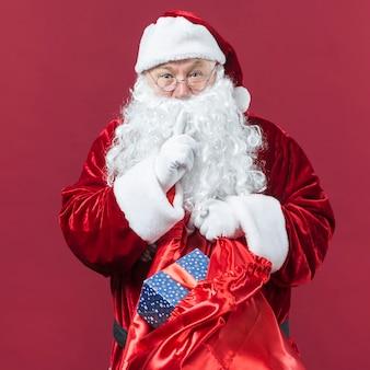 De kerstman in glazen met zak van giften die geheim gebaar tonen