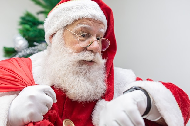 De kerstman is laat. hij kijkt bang naar de klok. santa claus draagt een moderne klok. countdown. de tijd komt.