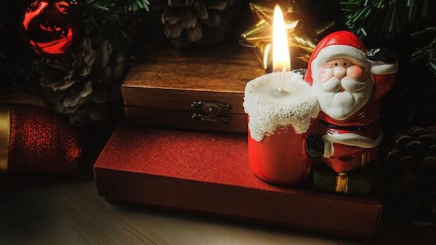 De kerstman-kaars op houten tafel voor kerstinhoud.